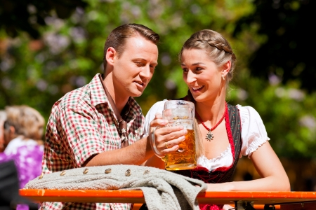 Happy Couple sitting in Beer garden and enjoy the beer and the sun photo