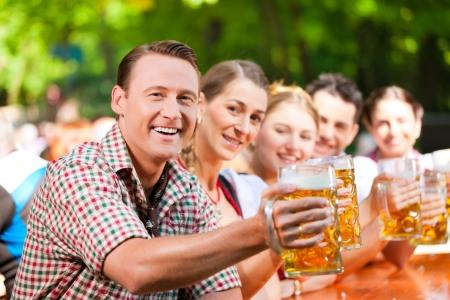 beer drinking: In Beer garden - friends in Lederhosen drinking a fresh beer in Bavaria, Germany