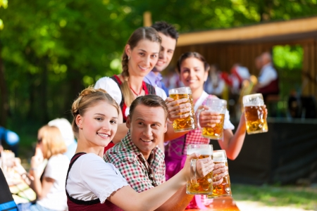 stein: In Beer garden in Bavaria, Germany - friends in Tracht, Dirndl and Lederhosen and Dirndl standing in front of band