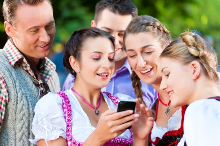 tracht: Friends in Beer garden looking a photograph on one's smartphone