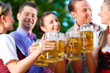 stein: In Beer garden - friends in Tracht, Dirndl and Lederhosen drinking a fresh beer in Bavaria, Germany