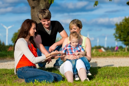 mother in law: Family - Grandmother, mother, father and child sitting and playing in garden
