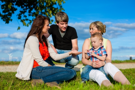 father in law: Family - Grandmother, mother, father and child sitting and playing in garden