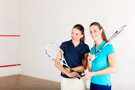 might: Two women playing squash as racket sport in gym; it might be a competition