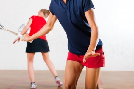 racket sport: Dos mujeres jugando al squash como deporte de raqueta en el gimnasio, puede ser que sea una competici�n