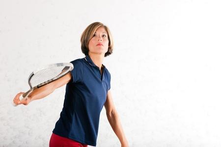 racket sport: Mujer madura que juega al squash como deporte de raqueta en el gimnasio, que podr�a ser una competencia