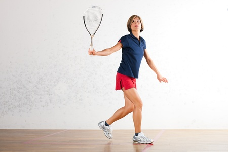 might: Mature woman playing squash as racket sport in gym, it might be a competition