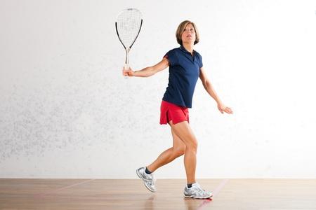 racket sport: Mujer madura jugando al squash como deporte de raqueta en el gimnasio, puede que sea una competencia Foto de archivo