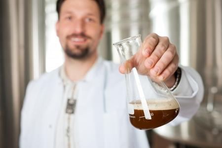 brewer: Brewer pie en su f�brica de cerveza y est� examinando la cerveza para su pureza Foto de archivo