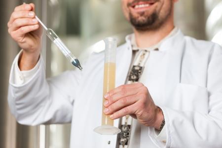 brewer: Brewer pie en su f�brica de cerveza y est� examinando la cerveza por su pureza