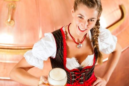 comida alemana: Mujer en Tracht bávaro, un cervecero femenino, con jarra de cerveza en cervecería