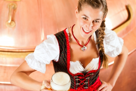 steins: Woman in Bavarian Tracht, a female brewer, with beer stein in brewery
