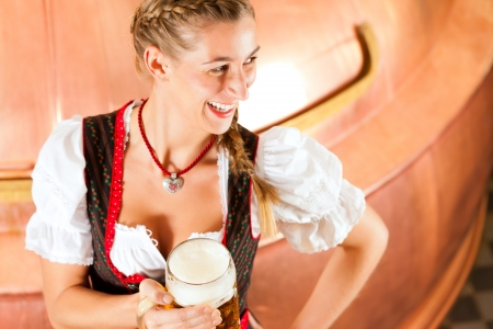brewer: Woman in Bavarian Tracht, a female brewer, with beer stein in brewery