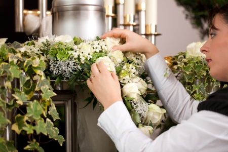 cremation: death and dolor  - mortician on funeral with urn preparing the flowers