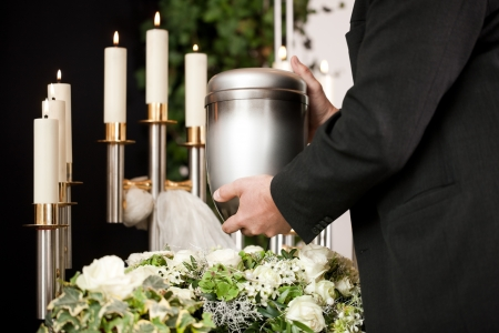 burial: death and dolor  - funeral and cemetery, mortician carrying the urn to a bed of white roses