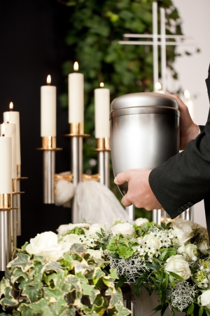 Religion, death and dolor  - mortician on funeral with urn photo
