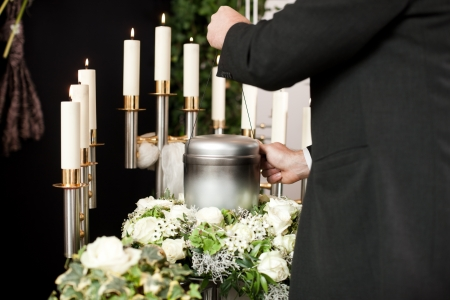 undertaker: Religion, death and dolor  - mortician on funeral with urn Stock Photo