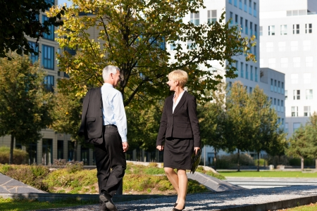 greets: Business people - mature or senior - pass by and greet Stock Photo