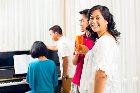middle class: Los asiáticos se sientan junto al piano y que se divierte y sonriente