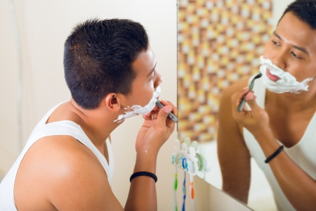 Asian man shaving in front of bathroom mirror photo