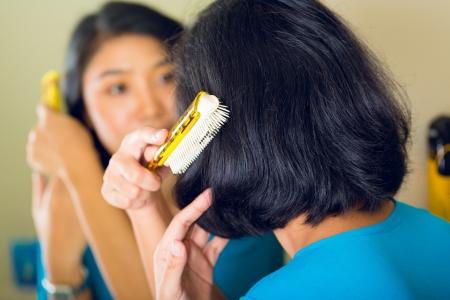 combing hair: Asian woman combing hair in front of mirror in her bathroom