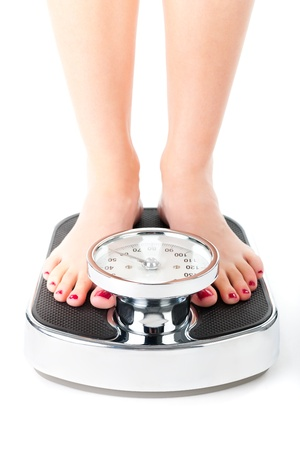 scale weight: Diet and weight, young woman standing on a scale, only feet to be seen