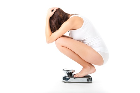 bulimia: Diet and weight, young woman sitting on her haunches on a scale, she is desperate