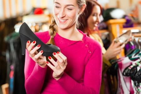 comprando zapatos: Trajes tradicionales - mujer joven es la compra de zapatos para ella Tracht o dirndl en una tienda