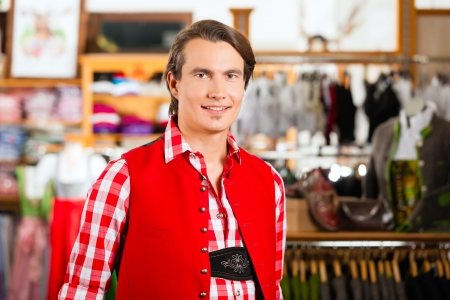 try on: Traditional clothes - young man is buying Tracht or lederhosen in a shop, he has to try it on before Stock Photo