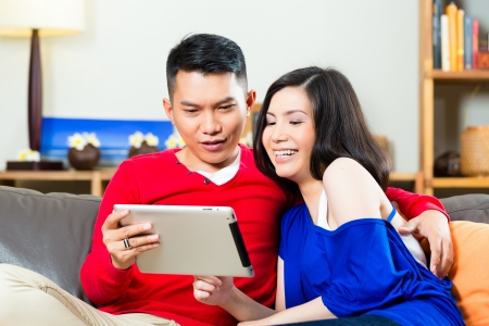 intimately: Young Indonesian couple - man and woman - sitting with a tablet computer on a couch