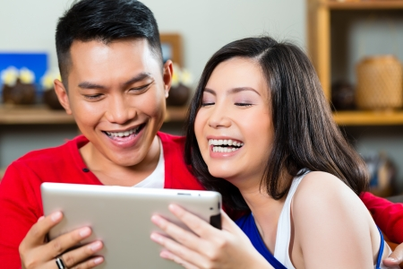 Young Indonesian couple - man and woman - sitting with a tablet computer on a couch Stock Photo - 19000735