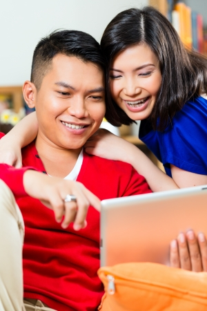 Young Indonesian couple - man and woman - sitting with a tablet computer on a couch Stock Photo - 19000728