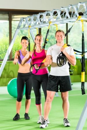 Gruppe von Menschen trainieren mit Schlingentrainer oder Suspension trainer in Fitnessstudio  photo