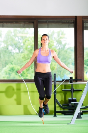 Woman jumping with rope, jumping rope in a fitness club or gym photo