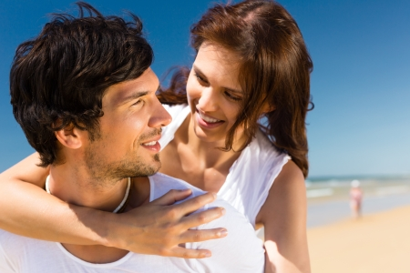easygoing: Playful couple on the ocean beach enjoying their summer vacation, the man is carrying the woman piggyback Stock Photo