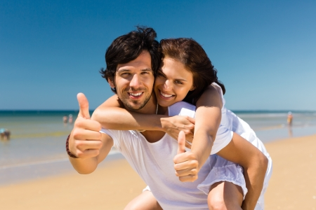 two thumbs up: Playful couple on the ocean beach enjoying their summer vacation, the man is carrying the woman piggyback Stock Photo