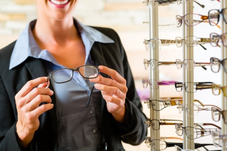 salesperson: Young woman at optician with glasses, she might be customer or salesperson Stock Photo