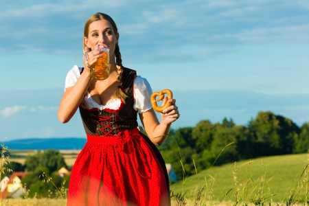 Young Bavarian woman drinking beer and keeping a pretzel in dirndl at meadow photo