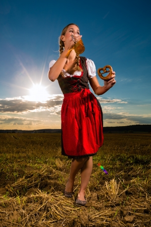 Young Bavarian woman drinking beer and keeping a pretzel in dirndl at meadow Stock Photo