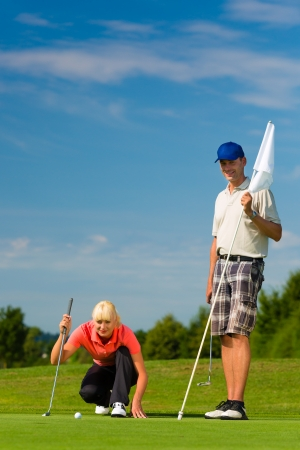 Young female golf player on course putting, she aiming for her put shot Stock Photo - 19000664