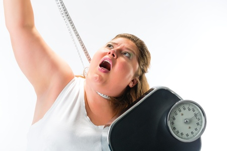 losing control: obese woman strangling herself with measuring tape and holding a weight scale Stock Photo