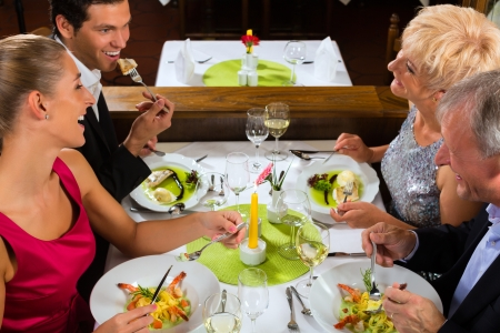 clinking: Family, mother and father with adult children and daughter or son in law –fine dining in nice restaurant or hotel