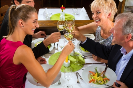 couple dining: Family, mother and father with adult children and daughter or son in law –fine dining in nice restaurant or hotel