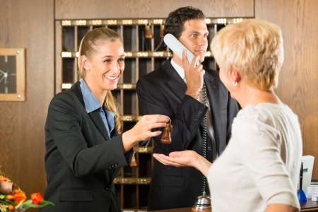 key cabinet: Reception - Guest checking in a hotel at the front desk, the service is friendly