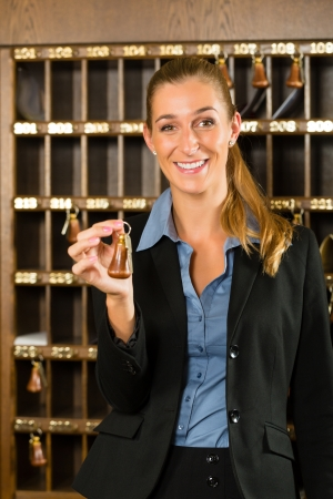 desk clerk: Reception of hotel - desk clerk, woman holding a key in the hand and smiling