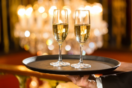party tray: Waiter served champagne glasses on a tray in a fine dining restaurant, a large chandelier is in Background