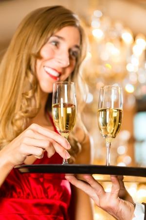 sektglas: Kellner serviert Champagner-Gläser auf einem Tablett in einem Gourmetrestaurant und Frau nimmt ein Glas, ist ein großer Kronleuchter im Hintergrund