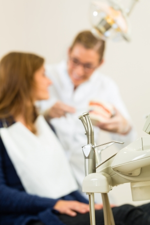 false teeth: various tools of a dentist waiting to be used in the surgery, in the background a Dentist is giving a female patient a treatment