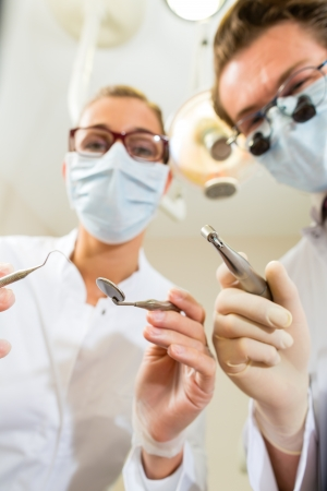 dentist drill: Dentist and assistant at a treatment, from the perspective of a patient Stock Photo