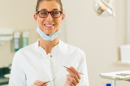 Dentists in his surgery holds a mirror and drill, she looking at the viewer Stock Photo - 19000647